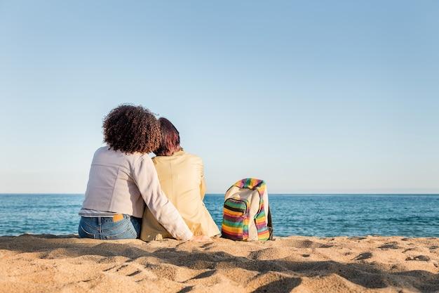 Coppia di ragazze gay che si siedono sulla spiaggia