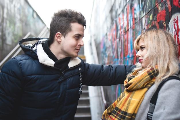 Coppia - ragazza e ragazzo stanno flirtando vicino al muro