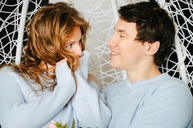 Coppia ragazza e ragazzo che si abbracciano su una grande sedia con un mazzo di rose. maglione bianco e blu.