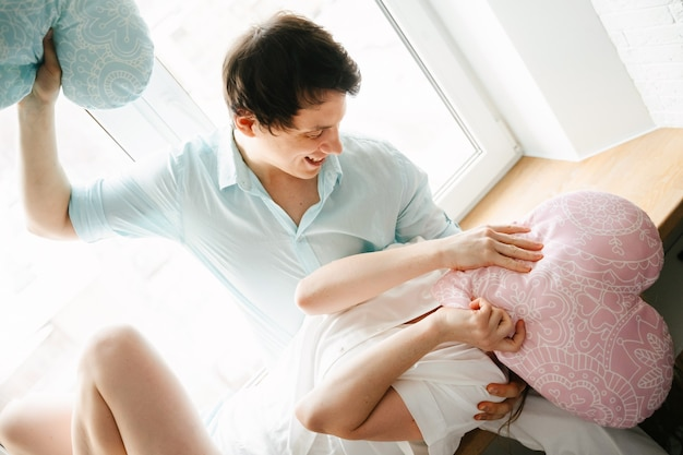 Coppia ragazza e ragazzo giocano con i cuscini vicino alla finestra. vestiti bianchi e blu. san valentino.