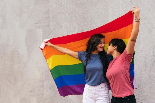 Un paio di ragazze che si guardano con una bandiera del gay pride all'aria aperta.