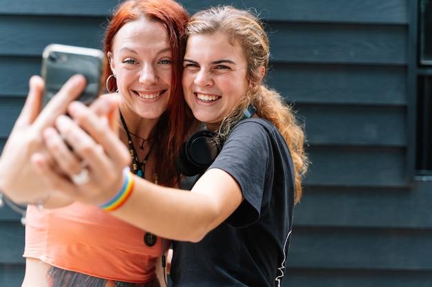 Coppia di ragazze con un braccialetto bandiera lgtb che si fanno un selfie con un telefono per strada