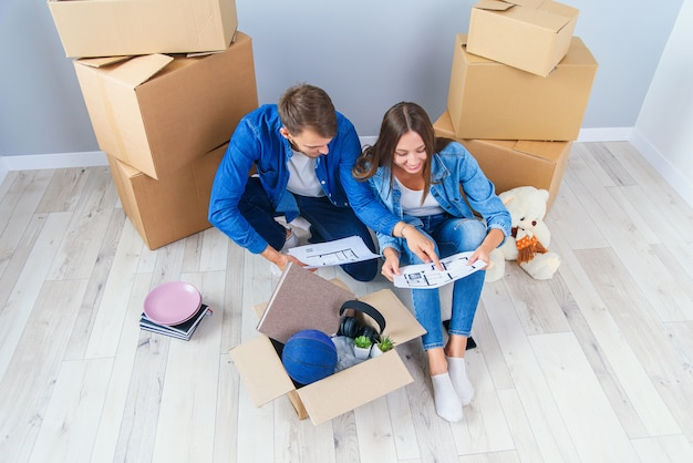 Le coppie discutono sul design della loro nuova casa seduta sul pavimento di legno tra molte scatole di cartone. belle giovani coppie alla moda nell'amore che progettano progettazione domestica per il loro nuovo appartamento acquistato.