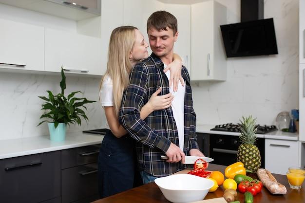 Coppia divertirsi nella cucina moderna mentre prepara succhi di frutta fresca e insalata di verdure