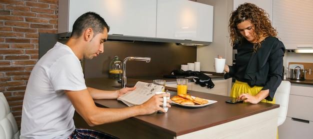 Coppia che fa colazione leggendo la notizia del confinamento del virus
