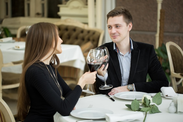 Coppia cenando in un ristorante e facendo un brindisi