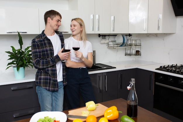 Coppia divertirsi in cucina bevendo vino rosso