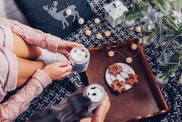 Coppie che mangiano cioccolata calda con biscotti sotto l'albero di natale