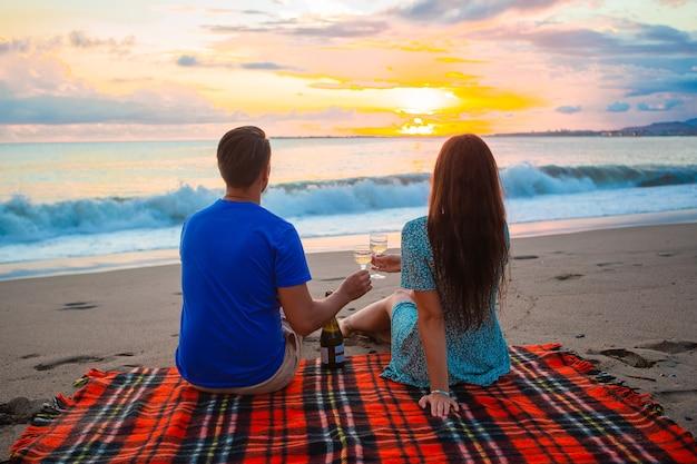 Coppia che fa un picnic sulla spiaggia bevendo vino