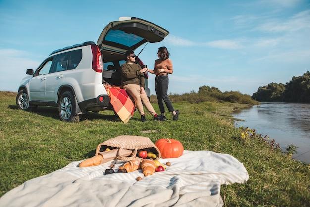 Coppia che fa un picnic allo spazio della copia della giornata calda autunnale della spiaggia del fiume