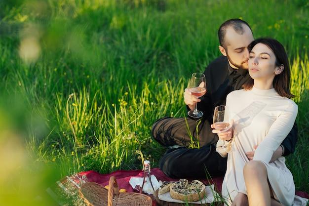 Coppia che fa un picnic romantico con una gustosa cheesecake e vino