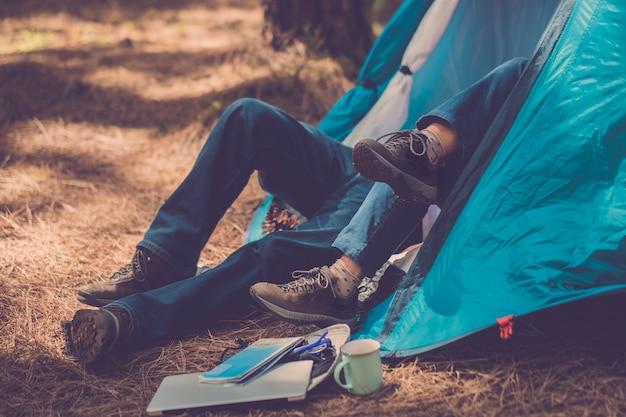 Coppia di escursionisti trekker godersi la tenda all'interno con amore e collaborazione insieme. laptop e mappa all'esterno pronti per iniziare e godersi l'esplorazione e la vacanza. lo stile di vita delle attività all'aperto godendosi