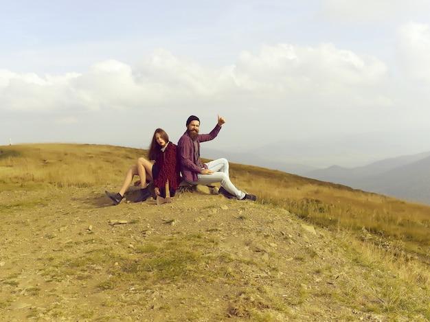 Hipsters delle coppie che si siedono sulla pietra sulla cima della montagna