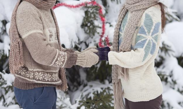 Coppia che si tiene per mano, l'inverno va in viaggio, godendosi una passeggiata, una coppia di innamorati