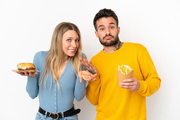 Coppia in possesso di hamburger e patatine fritte su sfondo bianco isolato avendo dubbi mentre si alzano le mani e le spalle
