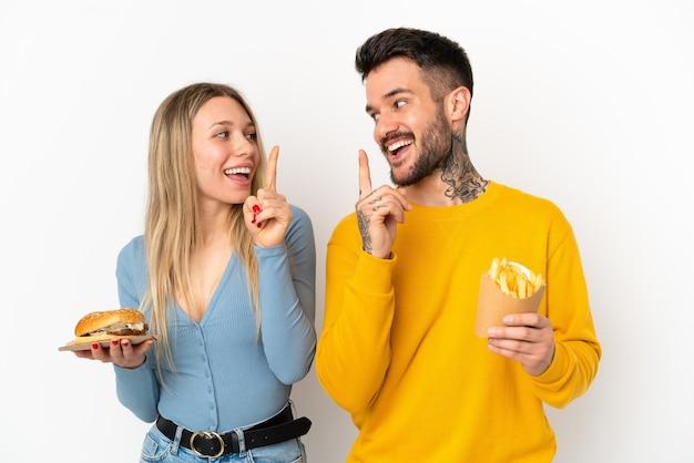 Coppia in possesso di hamburger e patatine fritte su sfondo bianco isolato con l'intenzione di realizzare la soluzione mentre si solleva un dito