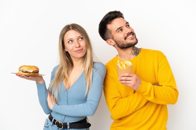 Coppia tenendo hamburger e patatine fritte su sfondo bianco isolato guardando in alto mentre sorride