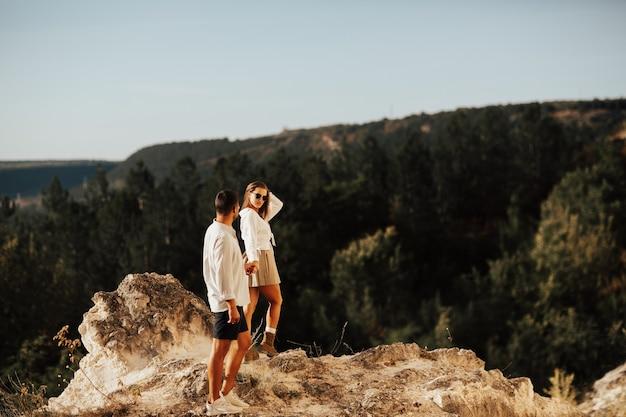 Coppia mano nella mano lungo la montagna rocciosa, sullo sfondo di bellissime montagne e cielo blu