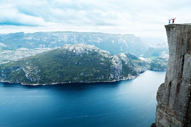 Coppia tenendosi per mano si trova sulla famosa roccia del pulpito di preikestolen sul lysefjord