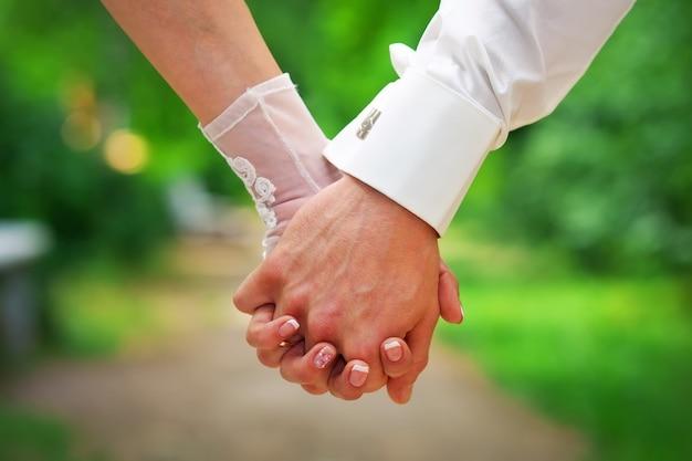 Coppia tenendosi per mano. due paia di mani innamorate si tengono insieme. sposi nel giorno del matrimonio