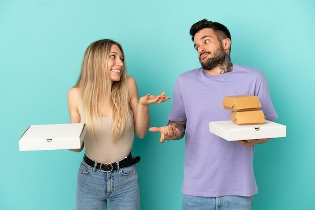 Coppia in possesso di pizze e hamburger su sfondo blu isolato facendo un gesto non importante mentre si sollevano le spalle