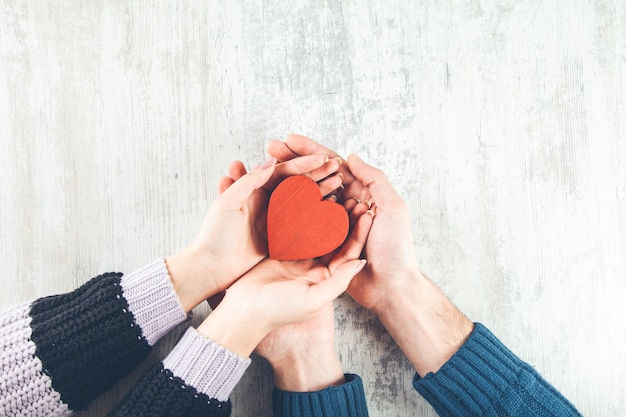 Coppie che tengono cuore rosso su superficie di legno
