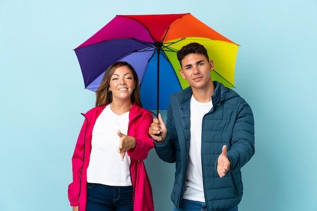 Coppie che tengono un ombrello sul blu che agitano le mani per chiudere un buon affare