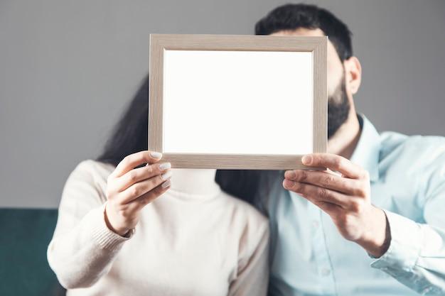 La coppia tiene la foto del telaio che si siede sul divano