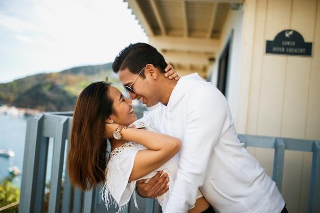 Coppia che abbraccia sul balcone con vista sull'oceano, ragazzo indiano bruna abbraccio ragazza asiatica in abiti bianchi.