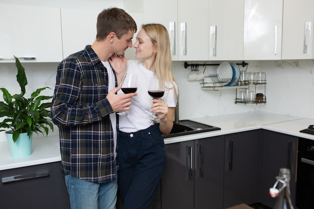 Coppia abbracciarsi in cucina e bere vino