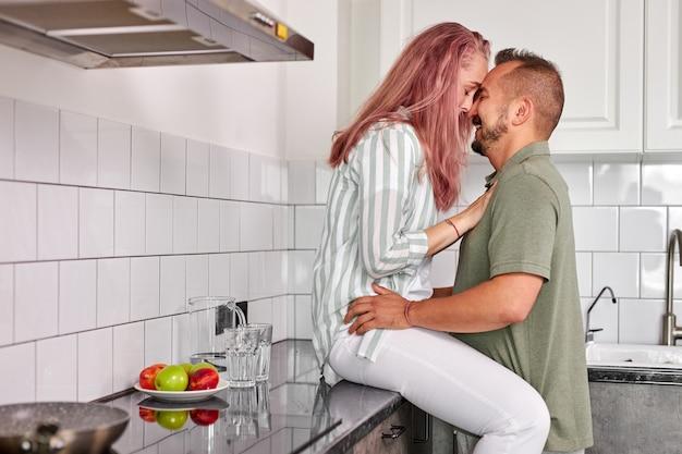 Le coppie che abbracciano in cucina, l'uomo romantico e la donna hanno tempo di relax al mattino