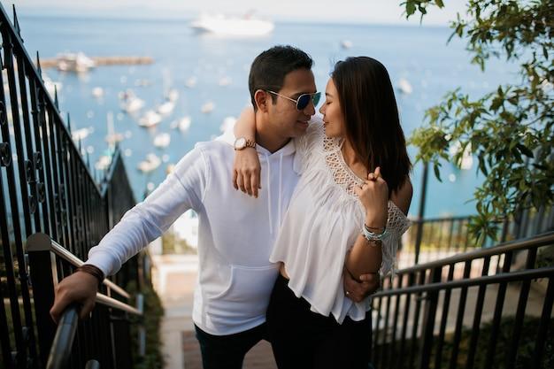 Coppia che abbraccia sulla scala con vista sull'oceano, ragazzo indiano bruna abbraccio ragazza asiatica data giovani con tempo soleggiato.