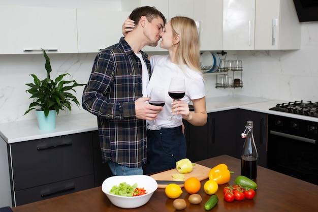 Coppia che abbraccia e vuole baciare in cucina mentre beve vino rosso
