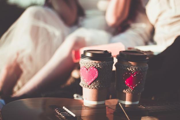 Coppia che si abbraccia mentre fa un picnic al tramonto tazza da caffè accogliente manica a maglia con cuore rosso in feltro