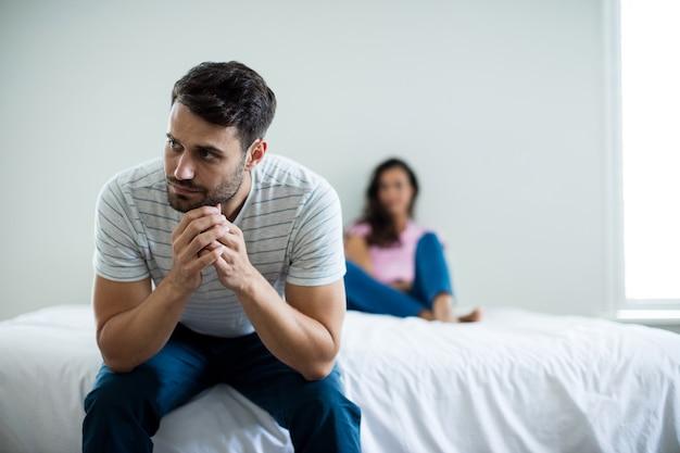 Coppia ignorandosi a vicenda in camera da letto a casa
