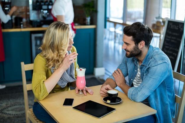 Coppia interagendo sorseggiando una tazza di caffè e un frappè