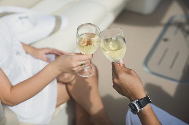 La coppia festeggia la luna di miele su uno yacht. bicchieri in luna di miele tintinnano wlovers festeggia la luna di miele su uno yacht. bicchieri di tintinnio della coppia di sposi con champagne e champagne