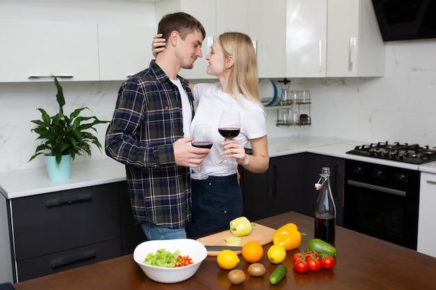 Coppia sta godendo di cucinare la cena insieme a casa e bere vino