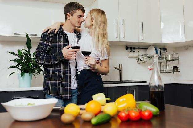 Coppia sta abbracciando in cucina e bevendo vino mentre cucina insalata fresca
