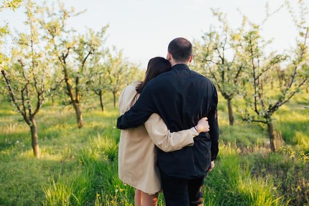 La coppia si abbraccia e cammina nella natura primaverile