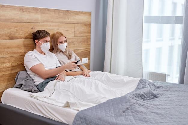 La coppia è messa in quarantena a casa, guarda la tv, seduta sul letto con indosso maschere mediche, isolata a causa della quarantena del coronavirus covid-19, epidemia. vista laterale