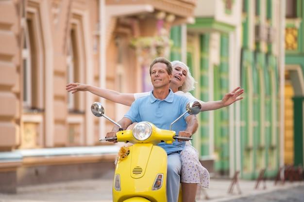 La coppia sta guidando uno scooter.