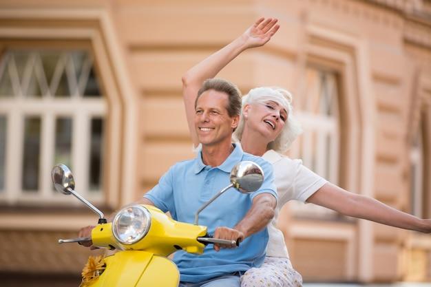 La coppia sta guidando il motorino giallo.