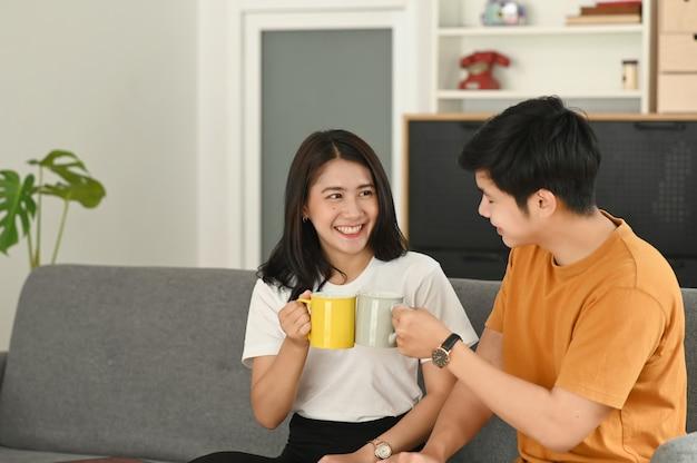 Una coppia è seduta e beve caffè sul divano di casa