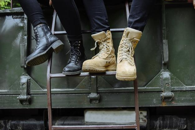 Coppia è seduta nel camion, le gambe negli stivali. turismo di montagna