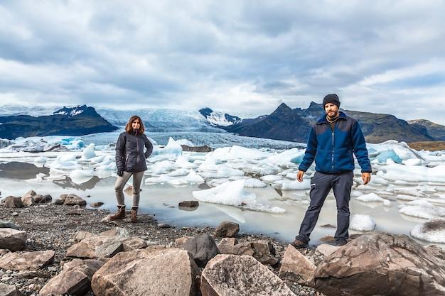 Una coppia nel lago degli iceberg jokulsarlon nel cerchio dorato dell'islanda meridionale