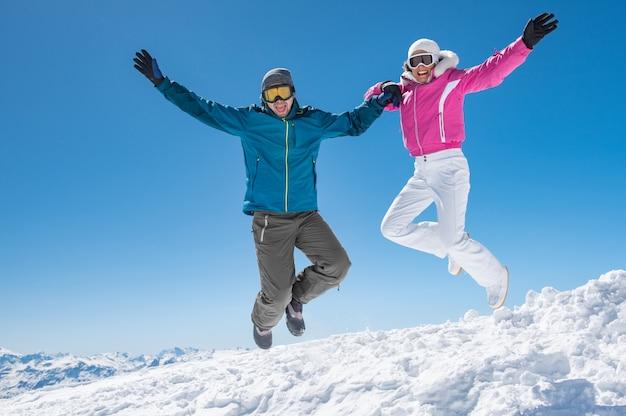 Coppia saltando sulla neve