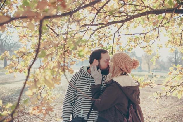 Coppia che si bacia nel parco d'autunno