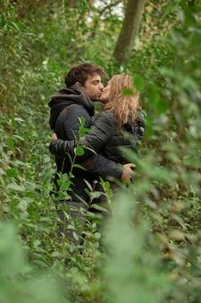 Coppia baciarsi e abbracciarsi nella foresta, tra le foglie degli alberi, indossando il cappotto invernale.