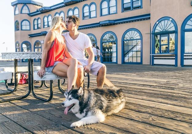 Coppia baciarsi in un appuntamento romantico all'aperto - amanti che camminano sul molo di santa monica con un cane husky - ritratto di famiglia moderna felice